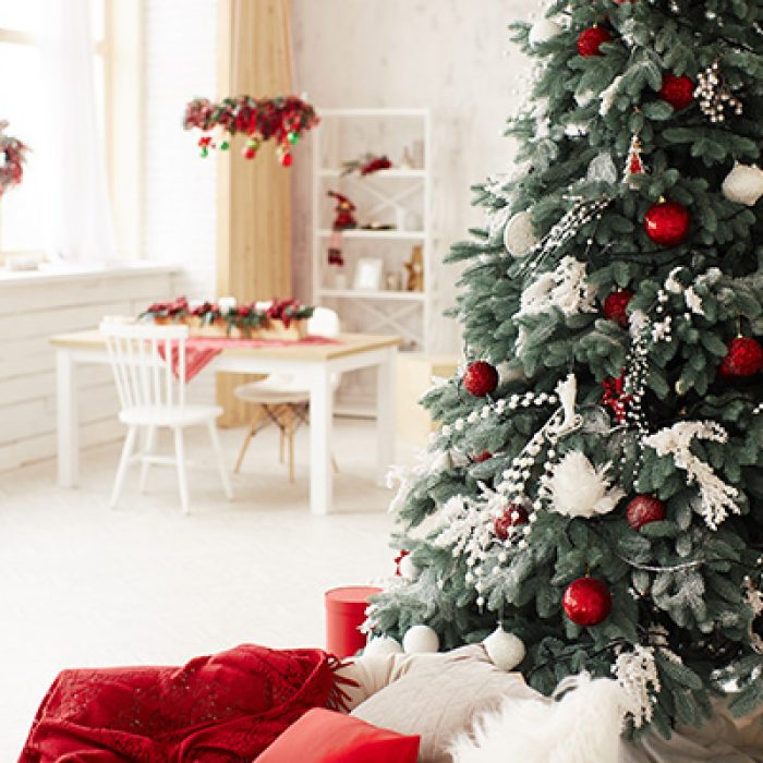 Winter holidays decor. Studio preparetions. Rich decorated New Year tree stands with present boxes in a cosy beige badroom
